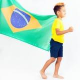 Brazilian patriot boy holding Brazil flag. Football or soccer championship Stock Photos