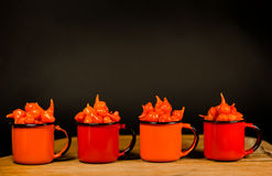 Brazilian Pimenta Biquinho red pepper - Capsicum chinese - on a cup. Photo with dark background Stock Image