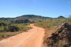 The Brazilian Royal Road between Diamantina and Cerro. Landscape of an  place of the Royal Road between Diamantina and Cerro, with a dusty road and blue skies at Royalty Free Stock Images