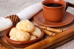 Brazilian snack pao de queijo (cheese bread). On brown plate with  cup of coffee on bamboo tray. Selective focus Stock Photo