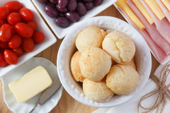 Brazilian snack pao de queijo (cheese bread). On white plate with cheese, ham, butter, cherry tomato and olives on wooden table. Selective focus Stock Photography