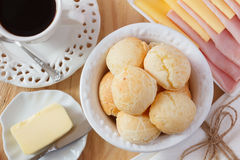 Brazilian snack pao de queijo (cheese bread). On white plate with cheese, ham, butter, cup of coffee on wooden table. Selective focus Royalty Free Stock Photography