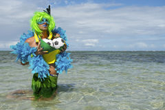 Brazilian Soccer Ball Football Drag Queen. Sexy Brazilian drag queen football fan with green wig and blue boa fondling her soccer balls in the shallow waters of Stock Image