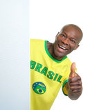 Brazilian soccer fan behind a blank signboard showing thumb Stock Images