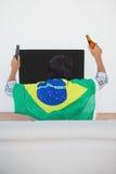 Brazilian soccer fan watching tv. Rear view of Brazilian soccer fan watching tv Royalty Free Stock Photos