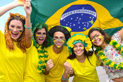 Brazilian soccer fans commemorating. Group of happy brazilian soccer fans commemorating victory, with brazilian flag in the background Royalty Free Stock Images