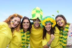 Brazilian soccer fans commemorating. Group of happy brazilian soccer fans commemorating victory, with brazilian flag in the background Stock Photo