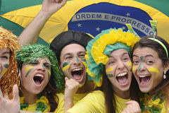 Brazilian soccer fans commemorating. Group of happy brazilian soccer fans commemorating victory, with brazilian flag in the background Stock Image