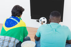 Brazilian soccer fans watching tv. Rear view of two Brazilian soccer fans watching tv Stock Photo
