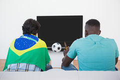 Brazilian soccer fans watching tv. Rear view of two Brazilian soccer fans watching tv Royalty Free Stock Photography