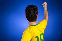 Brazilian soccer football athlete man celebrating. Brazilian soccer football athlete. One supporter and fan celebrating on blue background wearing yellow royalty free stock photo