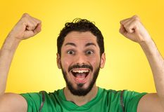 Brazilian soccer football athlete man celebrating. Brazilian soccer football athlete. One supporter and fan celebrating on yellow background wearing green royalty free stock photo