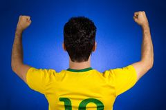 Brazilian soccer football athlete man celebrating. Brazilian soccer football athlete. One supporter and fan celebrating on blue background wearing yellow stock photos