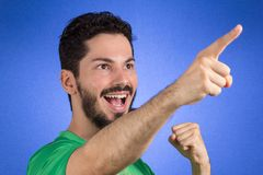 Brazilian soccer football athlete man celebrating. Brazilian soccer football athlete. One supporter and fan celebrating on blue background wearing green uniform stock photography