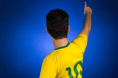 Brazilian soccer football athlete man celebrating. Brazilian soccer football athlete. One supporter and fan celebrating on blue background wearing yellow stock image