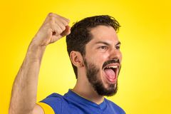 Brazilian soccer football athlete man celebrating. Brazilian soccer football athlete. One supporter and fan celebrating on yellow background wearing blue royalty free stock photography
