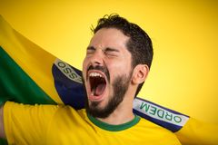 Brazilian soccer football player holding Brazil flag and shoutin. Brazilian soccer football team player. One supporter and fan holding Brazil flag. Wearing royalty free stock photography
