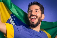Brazilian soccer football player holding Brazil flag. Brazilian soccer football team player. One supporter and fan holding Brazil flag. Wearing blue uniform on Stock Photos