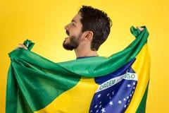 Brazilian soccer football player holding Brazil flag. Brazilian soccer football team player. One supporter and fan holding Brazil flag. Wearing blue uniform on stock photography