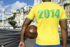 Brazilian Soccer Football Player Wearing 2014 Shirt Salvador. Brazilian soccer player holding football wearing 2014 shirt in Brazil colors Salvador Stock Image