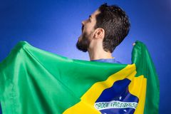 Brazilian soccer football player holding Brazil flag. Brazilian soccer football team player. One supporter and fan holding Brazil flag. Wearing blue uniform on Stock Images