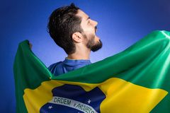 Brazilian soccer football player holding Brazil flag. Brazilian soccer football team player. One supporter and fan holding Brazil flag. Wearing blue uniform on Royalty Free Stock Images