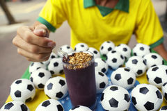 Brazilian Soccer Player Eating Acai with Footballs Royalty Free Stock Image