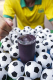 Brazilian Soccer Player Eating Acai Açaí with Footballs Stock Images