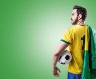 Brazilian soccer player holding the flag of Brazil and a ball on green background Royalty Free Stock Photos
