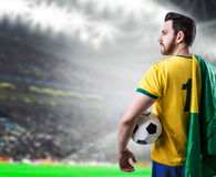 Brazilian soccer player holding the flag of Brazil and a ball in the stadium Stock Images