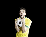 Brazilian soccer player holds a soccer ball. Sportive scene of a Brazilian soccer player holds a soccer ball. Can be used as a Australian uniform too stock photo