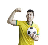Brazilian soccer player holds a soccer ball. Sportive scene of a Brazilian soccer player holds a soccer ball. Can be used as a Australian uniform too stock photography
