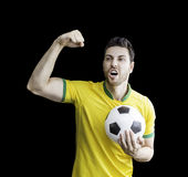 Brazilian soccer player holds a soccer ball. Sportive scene of a Brazilian soccer player holds a soccer ball. Can be used as a Australian uniform too stock photos
