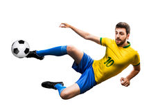 Brazilian soccer player in the jump kicks the ball on white background.  Royalty Free Stock Images