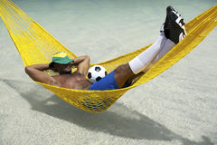 Brazilian Soccer Player Relaxing with Football in Beach Hammock Royalty Free Stock Image