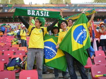 Brazilian soccer world cup fans. A group of fanatic Brazilian soccer fans supporting their national football team with flags and banners in the stadium. Photo Royalty Free Stock Images