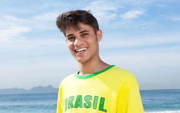 Brazilian sports fan at beach laughing at camera Stock Images