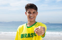 Brazilian sports fan at beach pointing at camera Stock Photo