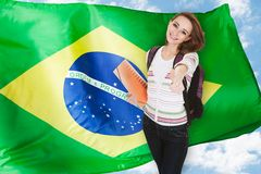 Brazilian Student Gesturing Thumb Up. Young Brazilian Female Student Gesturing Thumb Up In Front Of Brazil Flag Royalty Free Stock Photo