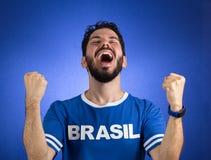 Brazilian supporter of National football team is celebrating, ch. Brazilian football fan emotions: celebrating, excited, happy. Supporter of Brazil national Royalty Free Stock Image