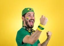 Brazilian supporter of National football team is celebrating, ch. Brazilian football fan emotions: celebrating, excited, happy. Supporter of Brazil national Stock Photography