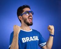 Brazilian supporter of National football team is celebrating, ch. Brazilian football fan emotions: celebrating, excited, happy. Supporter of Brazil national Stock Photos