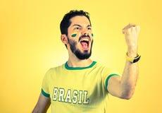 Brazilian supporter of National football team is celebrating, ch. Brazilian football fan emotions: celebrating, excited, happy. Supporter of Brazil national Stock Image