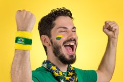 Brazilian supporter of National football team is celebrating, ch. Brazilian football fan emotions: celebrating, excited, happy. Supporter of Brazil national Royalty Free Stock Image
