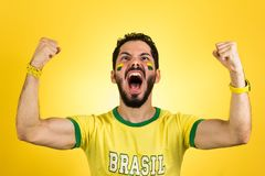 Brazilian supporter of National football team is celebrating, ch. Brazilian football fan emotions: celebrating, excited, happy. Supporter of Brazil national royalty free stock photo