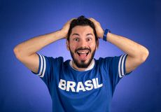 Brazilian supporter of National Team of football is surprised. Soccer fan in action emotions: happy, amazed. Supporter of Brazil National Team of football is Royalty Free Stock Image