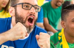Brazilian supporters at stadium bleachers. Goal, victory, celebr. Group of fans cheer for brazilian team on stadium bleachers. Emotions portrait. Goal, victory Stock Images