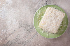 Brazilian traditional dessert: sweet couscous tapioca pudding. Cuscuz doce with coconut on marble table. Selective focus. Copy space Royalty Free Stock Images
