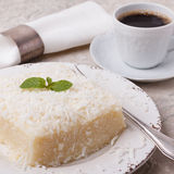 Brazilian traditional dessert: sweet couscous tapioca pudding. Cuscuz doce with coconut on plate with cup of coffee on marble table. Selective focus Royalty Free Stock Image