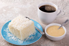 Brazilian traditional dessert: sweet couscous tapioca pudding. Cuscuz doce with coconut on plate with cup of coffee on marble table. Selective focus Stock Photos